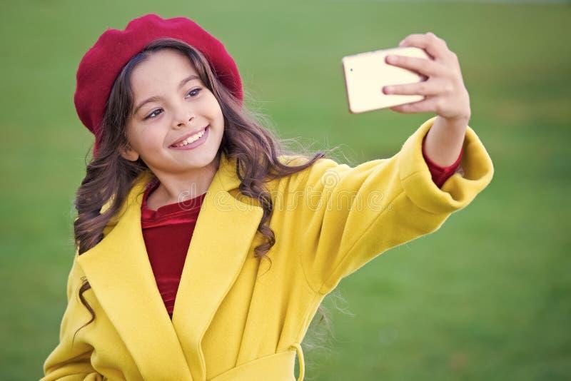 Smartphone o telefono cellulare della tenuta della bambina Comunicazione moderna della generazione Concetto di comunicazione su m immagine stock libera da diritti