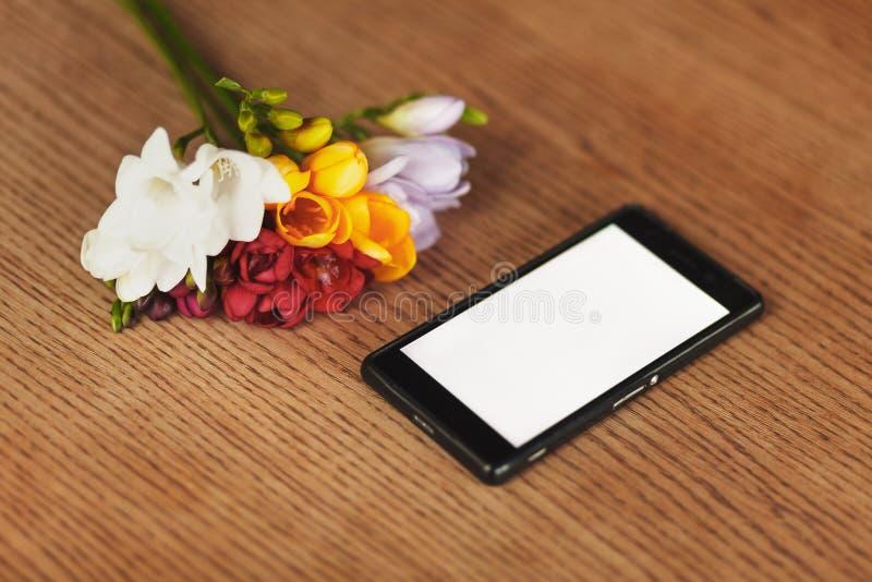 Smartphone och blommor på tabellen royaltyfri foto