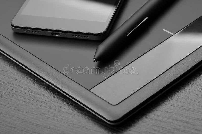 Smartphone och digital teckningsminnestavla för digitizer med en sakkunnig penna-som nålen på en trätabell Detaljer av arbetsplat royaltyfri fotografi