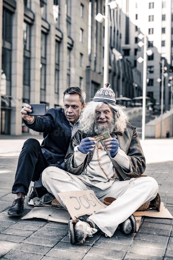 Smartphone och fotografera för galen kort-haired gamal man bärande fotografering för bildbyråer
