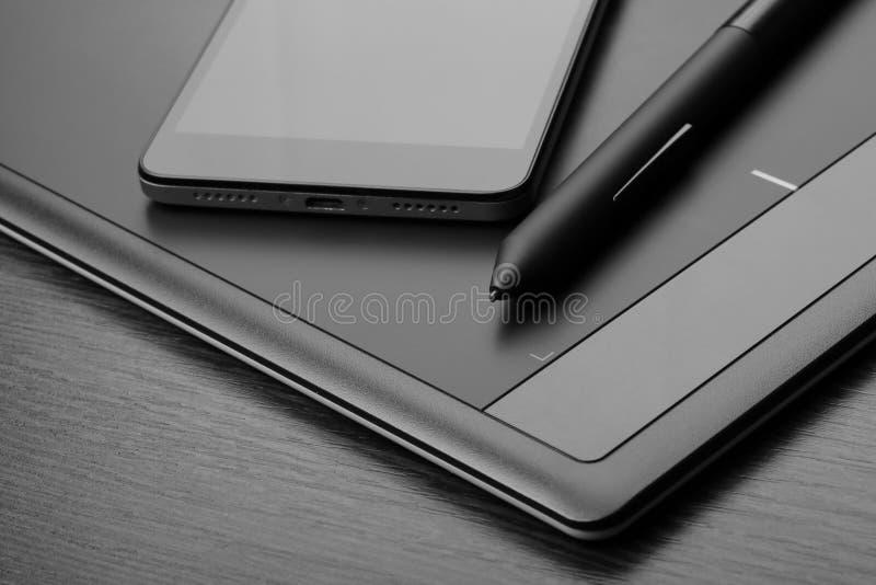 Smartphone och grafisk minnestavla också som är bekanta som en digitizer eller ett digitalt konstbräde med en sakkunnig penna-som arkivbild