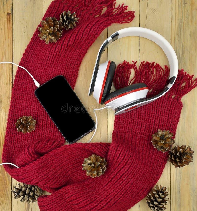 Smartphone och hörlurar Vinter Arbete går musik Modern te arkivbilder