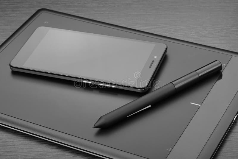 Smartphone och pennminnestavla också som är bekant som en grafisk minnestavla eller en digitizer med en sakkunnig penna-som nålen fotografering för bildbyråer