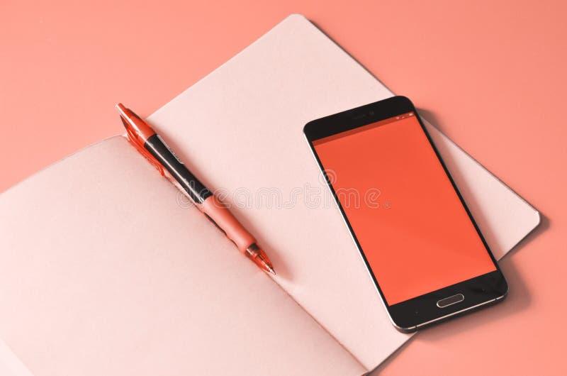 Smartphone och rosa anteckningsbok p? arbetetabellen royaltyfri bild