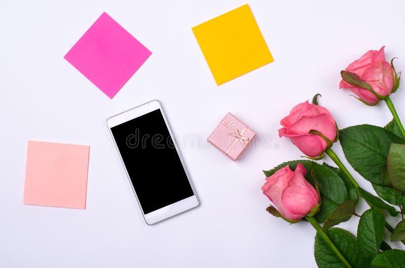 Smartphone och rosa rosor på en vit bakgrund arkivbilder