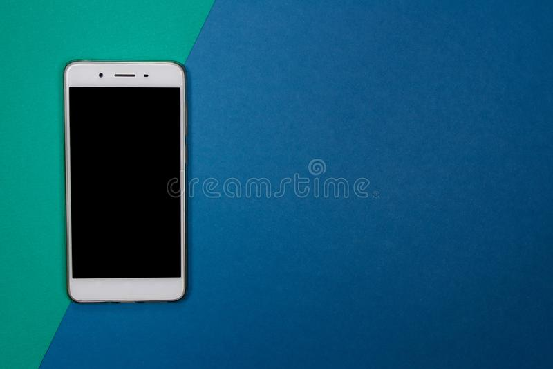 Smartphone oder Handy auf grünem und blauem Hintergrund mit Spindel stockbild