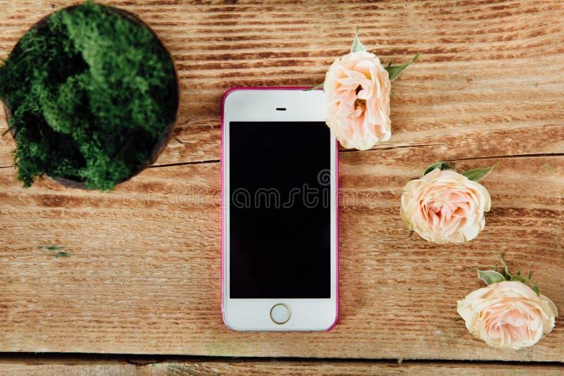 Smartphone op de houten lijst van een bloemwinkel naast een installatie stock fotografie
