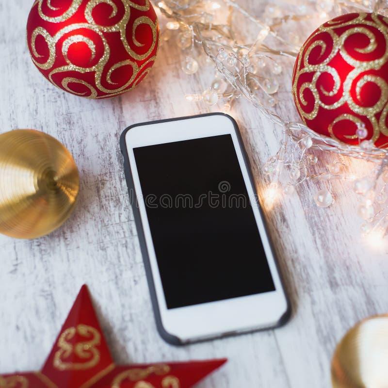 Smartphone op een witte houten achtergrond met Kerstmisspeelgoed en lichten royalty-vrije stock fotografie