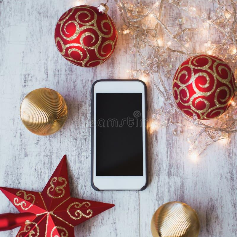 Smartphone op een witte houten achtergrond met Kerstmisspeelgoed en lichten stock foto