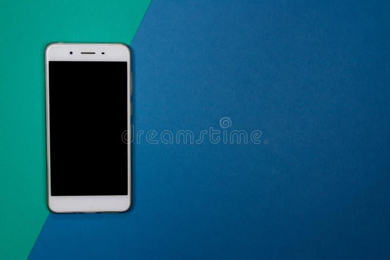 Smartphone ou téléphone portable sur le fond vert et bleu avec la cannette de fil image stock