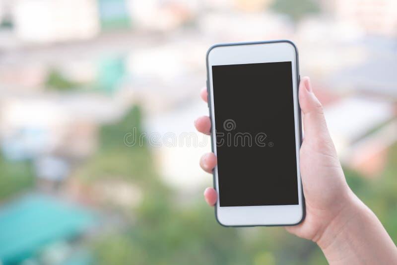 Smartphone ou telefone celular da terra arrendada da mão com fundo da construção da cidade e espaço da cópia fotografia de stock