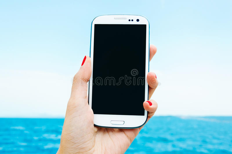 Smartphone på semester arkivbild