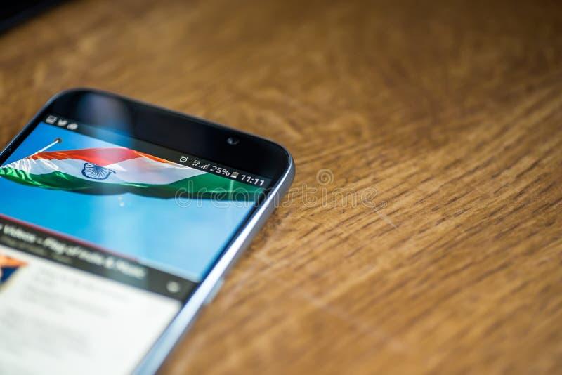 Smartphone på träbakgrund med tecknet för nätverket 5G 25 procent laddning och Indien sjunker på skärmen arkivfoton