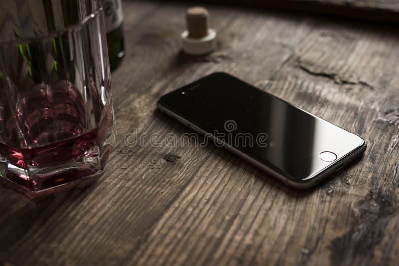 smartphone på trätabellen med whisky royaltyfri foto