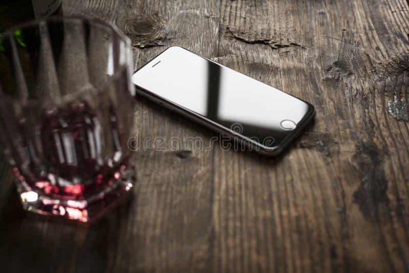 smartphone på trätabellen med whisky royaltyfria bilder