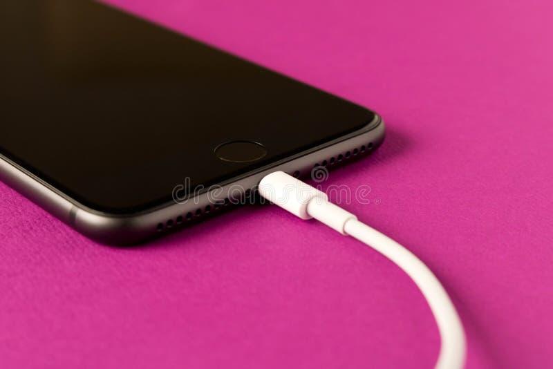 Smartphone p? laddning p? en purpurf?rgad bakgrund close upp royaltyfri fotografi