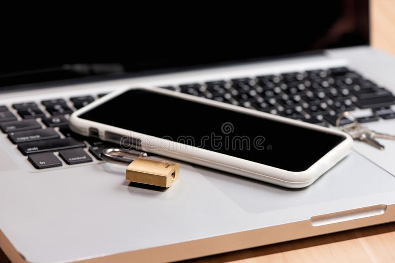 Smartphone and padlock is lying on a laptop keyboard.  stock images
