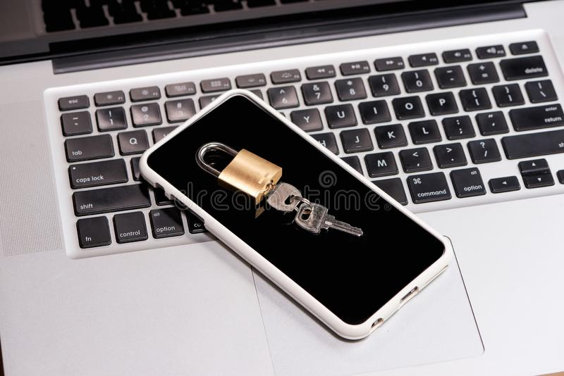 Smartphone and padlock is lying on a laptop keyboard.  royalty free stock photos