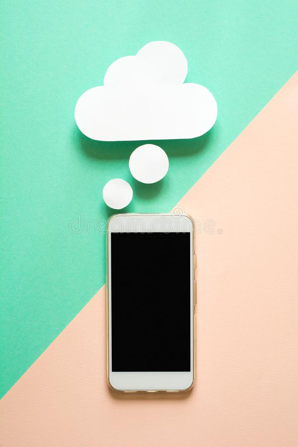 Smartphone with paper dream bubbles on blue background. Phone dreaming on charge. Recharging concept. stock images