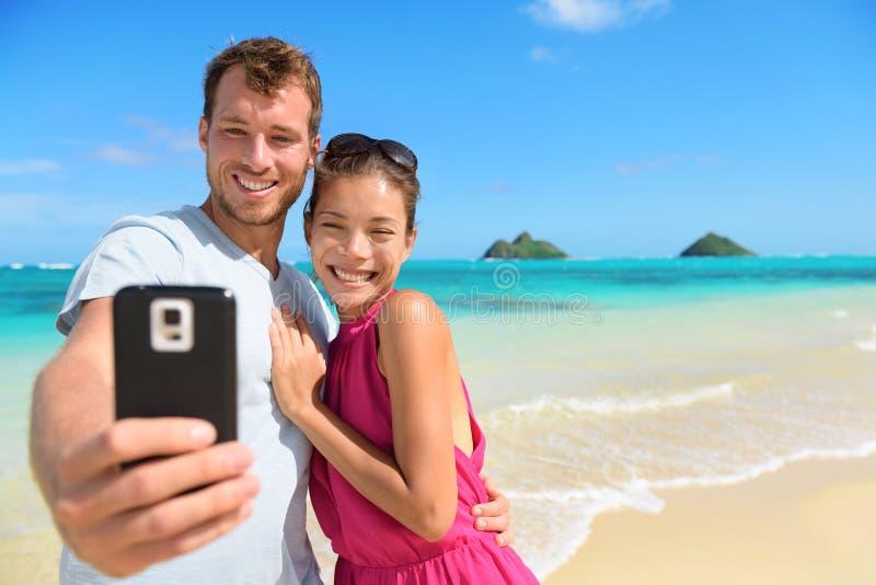 Smartphone - par de las vacaciones de la playa que toma el selfie fotografía de archivo libre de regalías