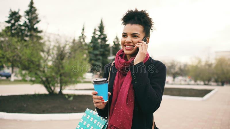 Smartphone parlant attrayant de femme d'affaires de métis et promenades potables de café dans la rue de ville avec des paniers photos libres de droits