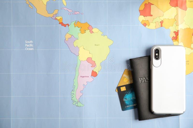 Smartphone, pasaporte y tarjetas de crédito en mapa del mundo Agencia de viajes foto de archivo