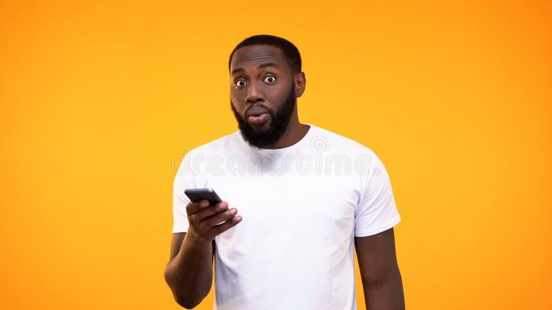 Smartphone pasmado de la tenencia del hombre joven a disposición, uso de las actividades bancarias, devolución de efectivo imagen de archivo