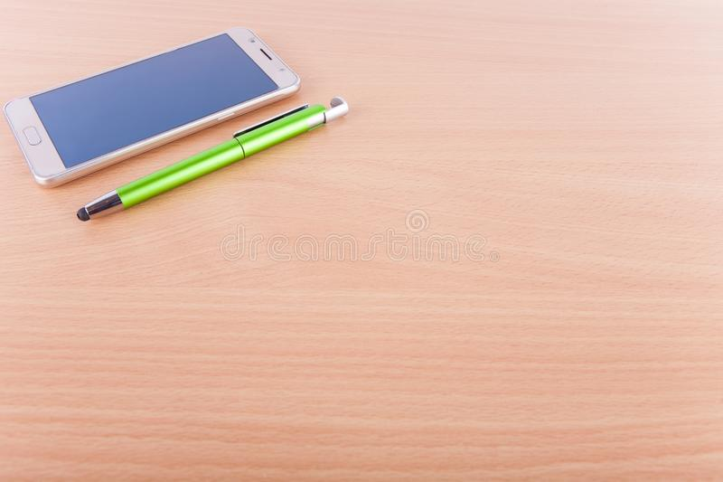 Smartphone and a pen with a large blank office desk area royalty free stock photos