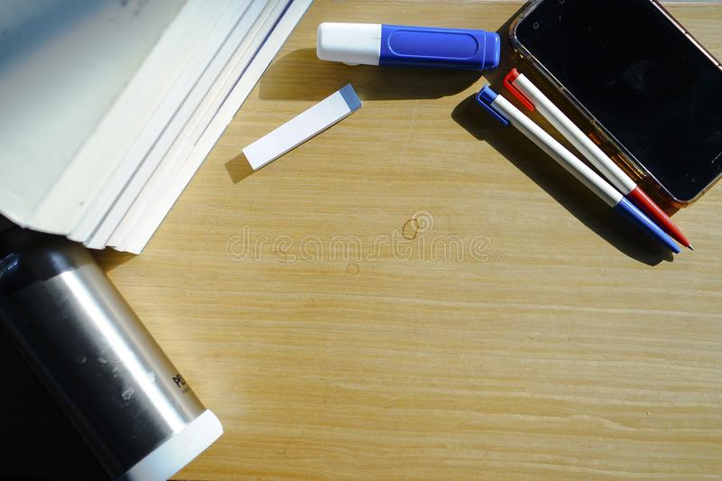 A smartphone, two different color pens, and a pile of books are placed on a wooden table. A smartphone, a pile of books, two different color pens, an iron water stock photography