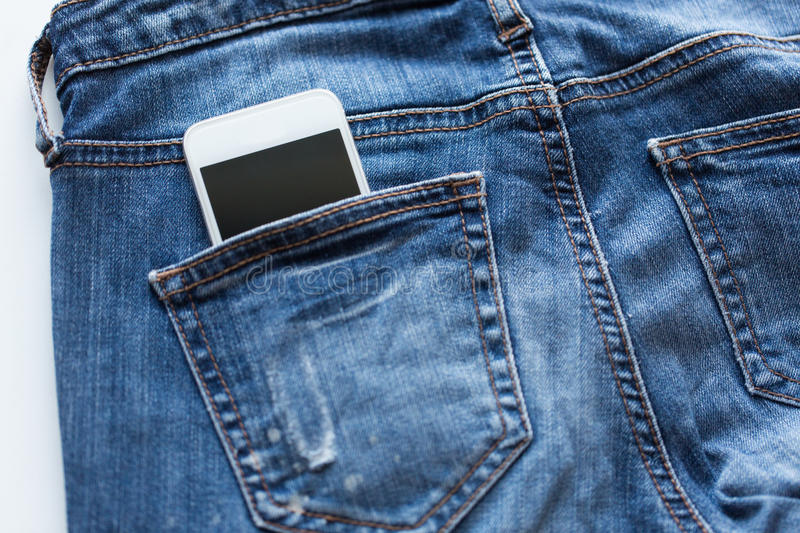 Smartphone in pocket of denim pants or jeans. Technology and communication concept - smartphone in pocket of denim pants or jeans stock photography