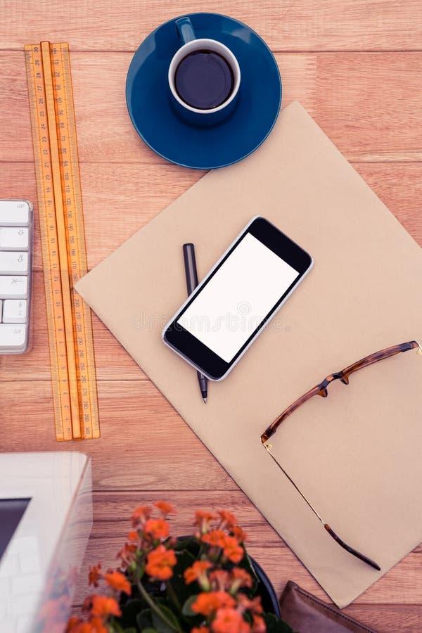 Smartphone por vidros do olho no papel pelo copo de café na mesa fotos de stock royalty free