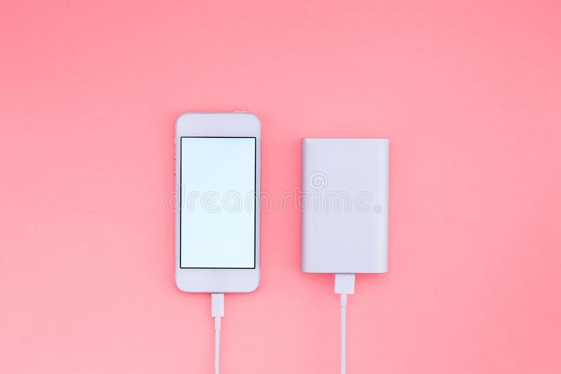 Smartphone and Powerbank on pink background. Powerbank charges the phone against the background. Flat lay. Smartphone and Powerbank on pink background. Powerbank royalty free stock image
