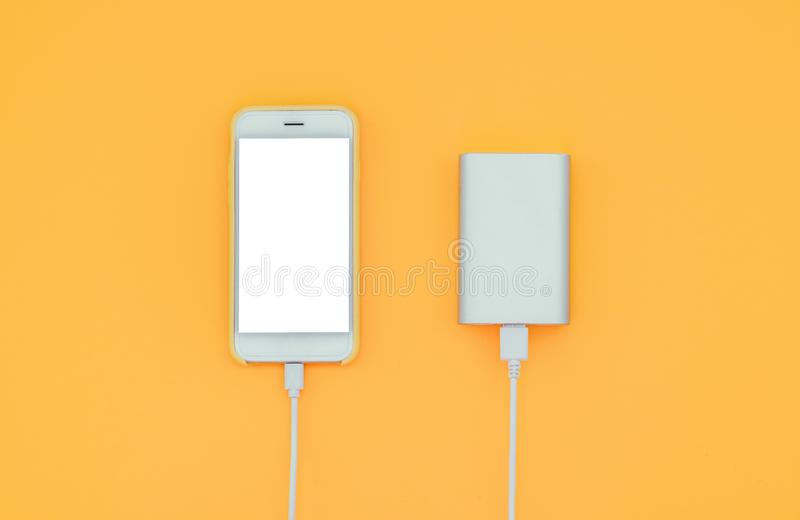 Smartphone and Powerbank on yellow background. Powerbank charges the phone against the background.  royalty free stock image