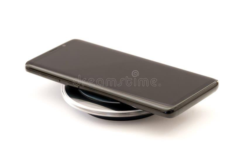 Smartphone preto moderno que carrega na almofada sem fio do carregador Isolado no fundo branco com trajeto de grampeamento imagem de stock