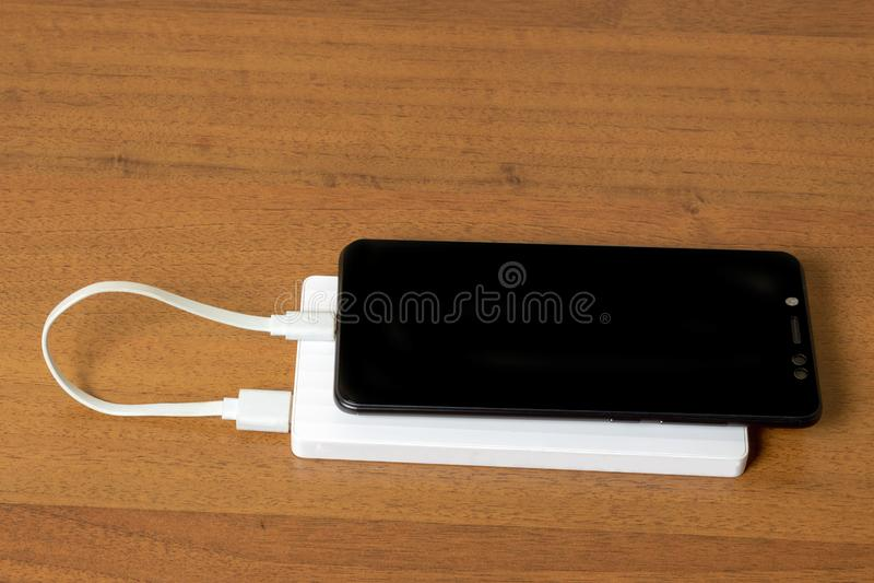 Smartphone preto que carrega com o banco branco do poder atrav?s do cabo de USB, vista superior foto de stock royalty free