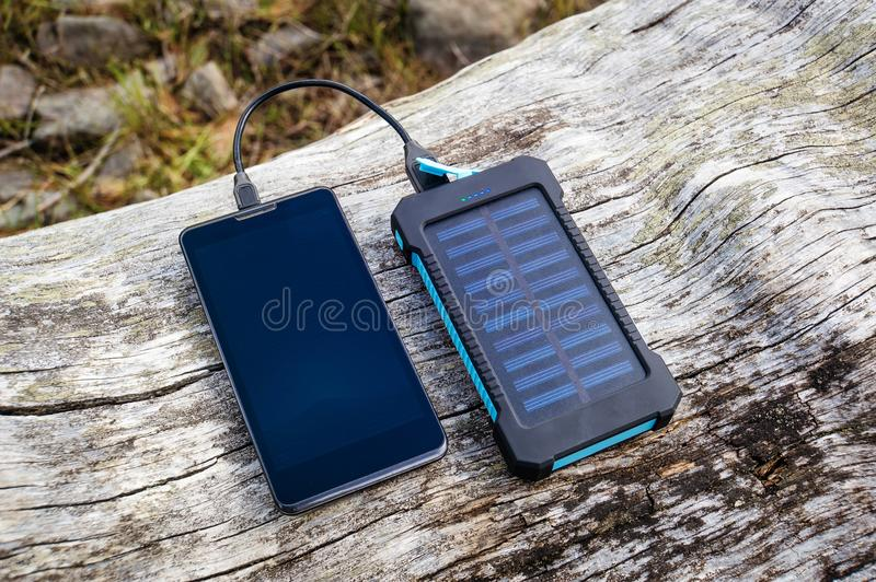Smartphone que carrega com o banco cor-de-rosa do poder no fundo de madeira imagem de stock