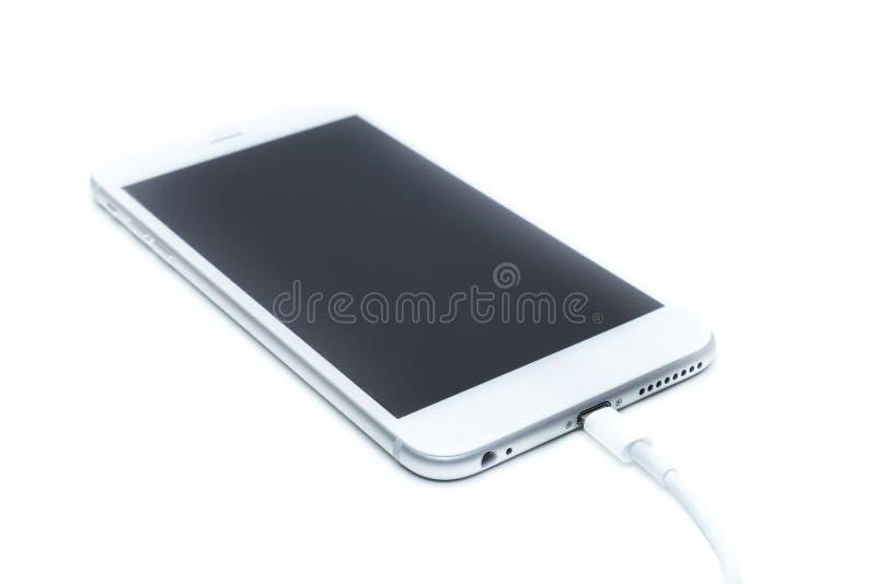 Smartphone que carrega com o isolado do cabo fotografia de stock
