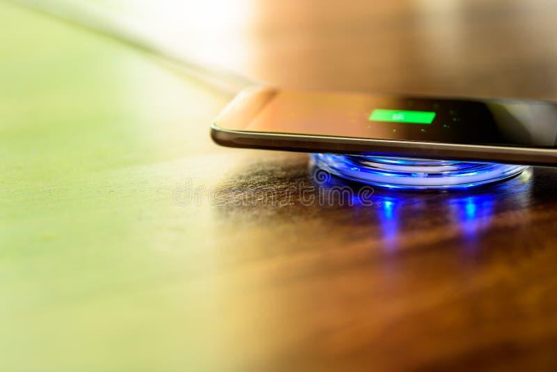 Smartphone que carrega em uma almofada de carregamento Cobrar sem fio fotos de stock royalty free
