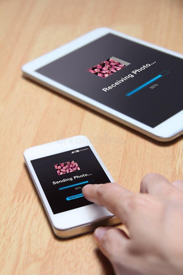Smartphone que envía la foto al otro dispositivo foto de archivo libre de regalías