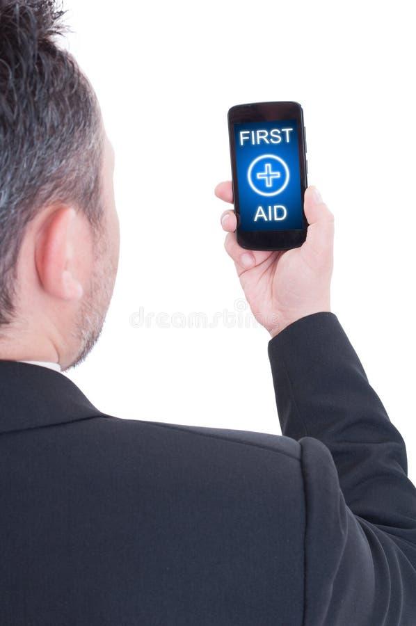 Smartphone que se sostiene masculino con el texto de los primeros auxilios foto de archivo