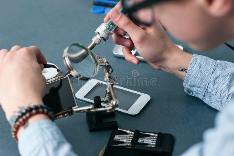 Smartphone quebrado de solda no close up da oficina de reparações fotos de stock royalty free