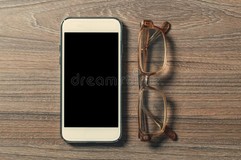 Smartphone and reading glasses on an old wooden board stock image