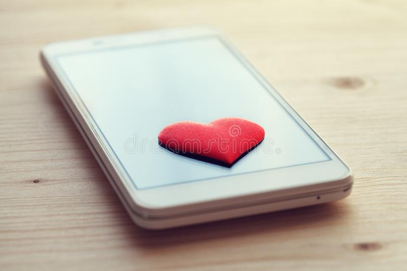 Smartphone with red heart on screen. Social media, online dating concept, like and thumb for posts, instagram, feedback stock photos