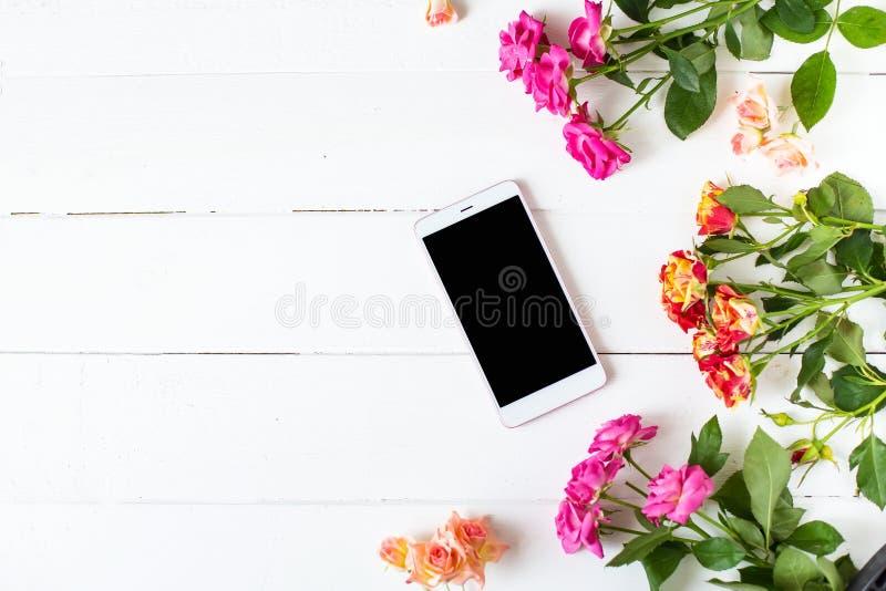 Smartphone rosor på tabellen Kvinnors saker danar kvinnors den skrivbords- siktsmodellen arkivbild
