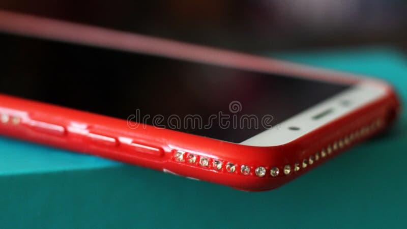 Smartphone rouge avec des fausses pierres si étroites photos stock
