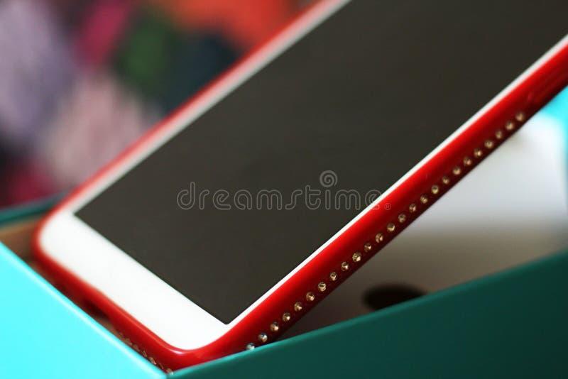 Smartphone rouge avec des fausses pierres si étroites images stock