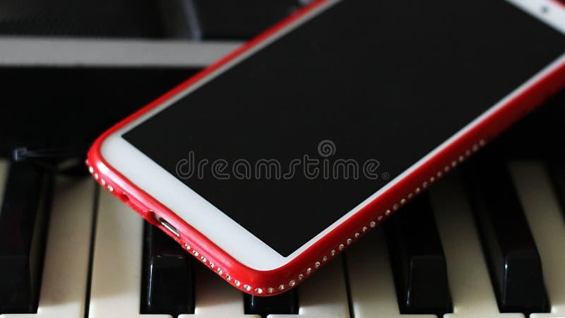 Smartphone rouge avec des fausses pierres sur le piano images stock