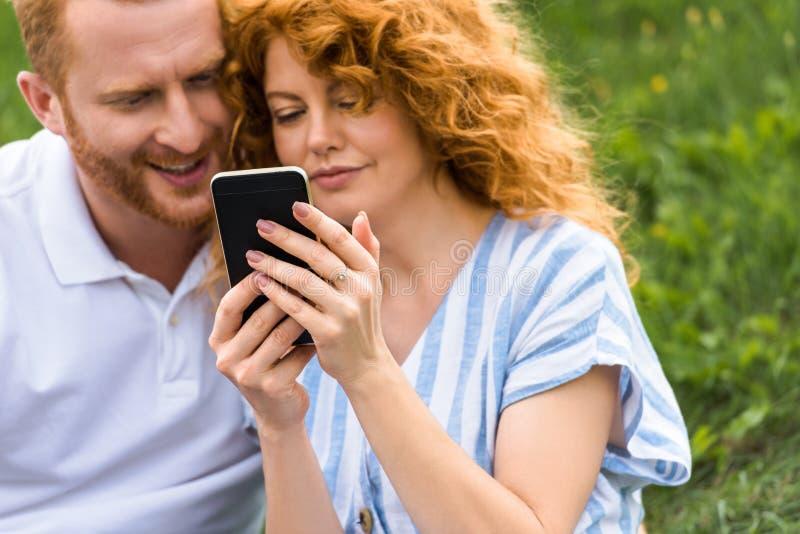 smartphone roux attrayant d'apparence de femme à l'ami de sourire photos libres de droits