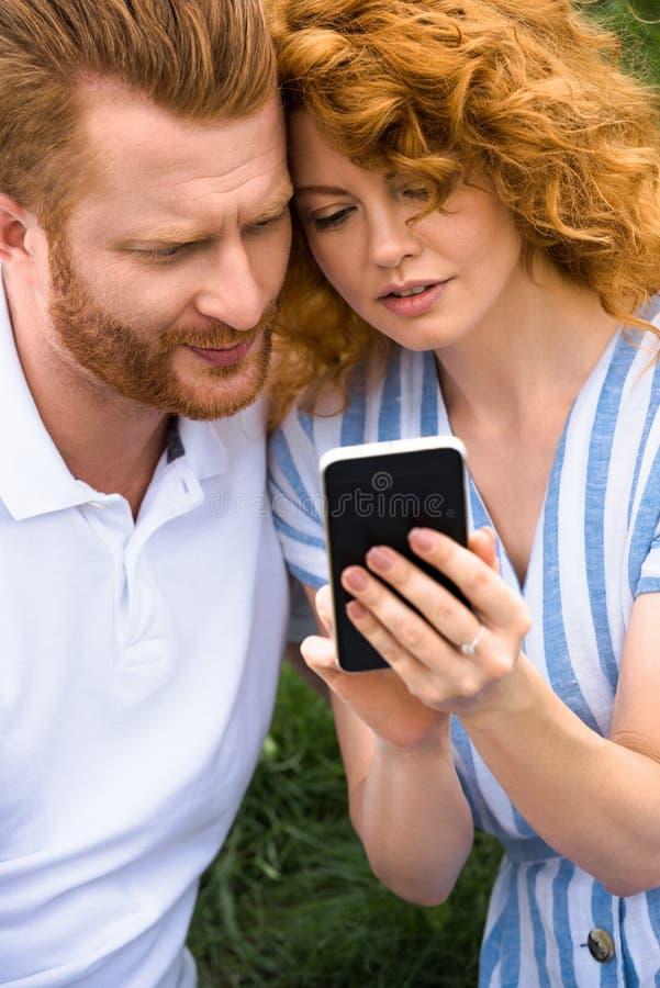 smartphone roux d'apparence de femme à l'ami photographie stock