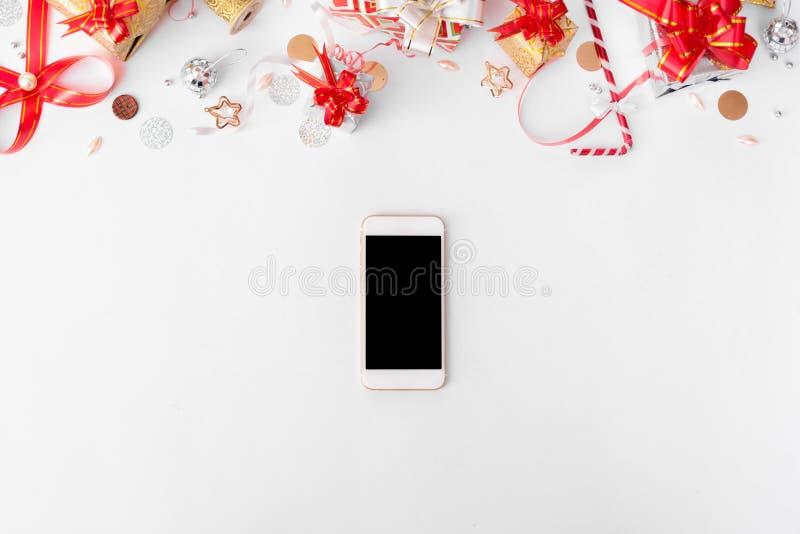 Smartphone-samenstelling voor Kerstmistijd Kerstmisgiften en decoratie op witte achtergrond stock foto's